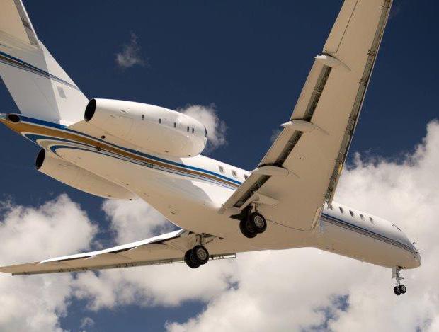 Sous les nuages épars un airbus traverse le ciel d'un bleu profond. Le train d'atterrissage est sorti. L'avion est photographié du dessous. Le photographe Forcdan a baptisé cette photo close landing. Sur la photo apparait le logo LGM Group.