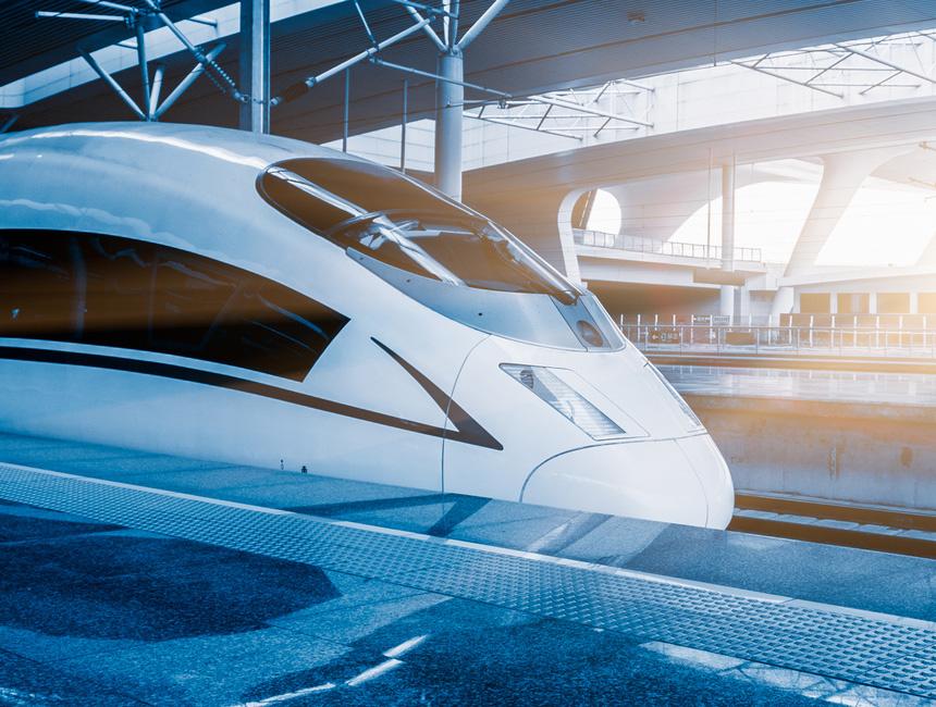 Le train à grande vitesse aux lignes futuristes entre en gare. Le soleil entre par le fond de la gare et baigne l'image d'une belle lumière blanche. La photo est quasiment bi-chromatique : dégradés de bleus et dégradés de blancs. Sur la photo apparait le logo Railenium.